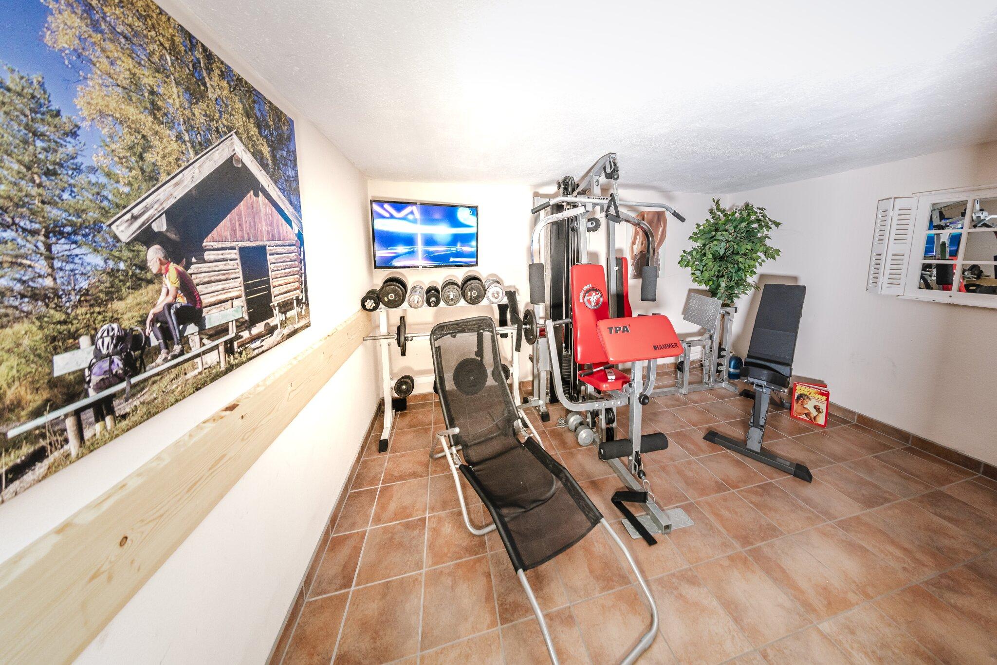 Fitnessraum mit TV und Liegestühlen