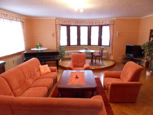 Wohnzimmer mit Flügel und Flachbildfernseh