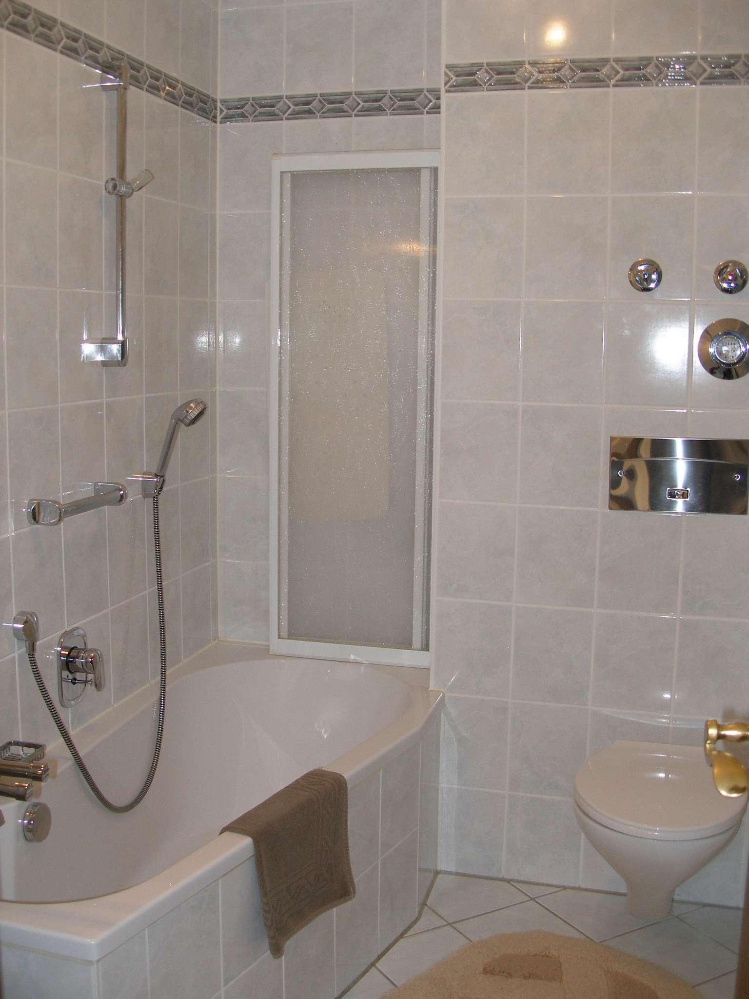 Modernes Bad mit Badewanne und Duschwand
