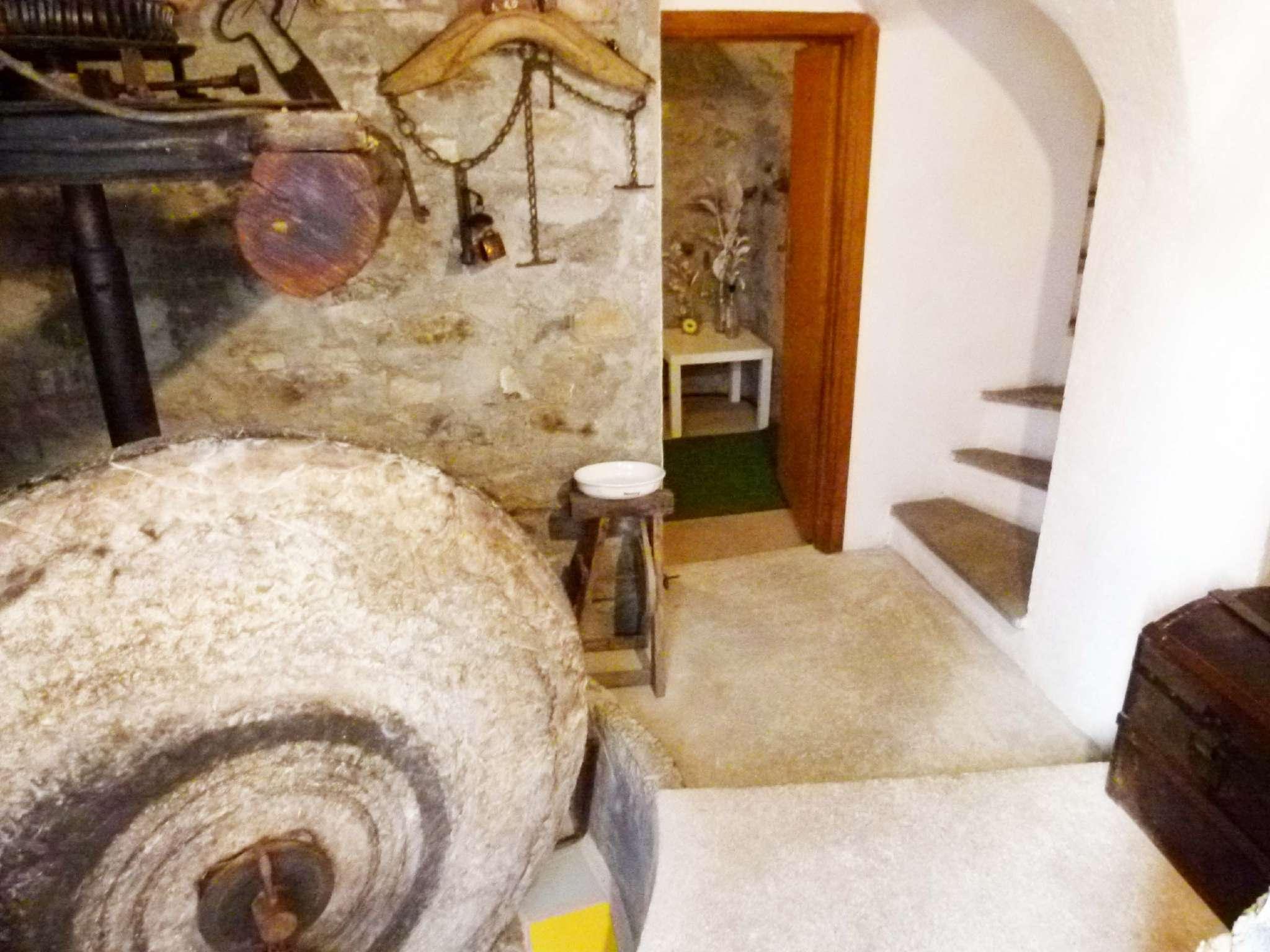 Eingang mit antiker Olivenpresse