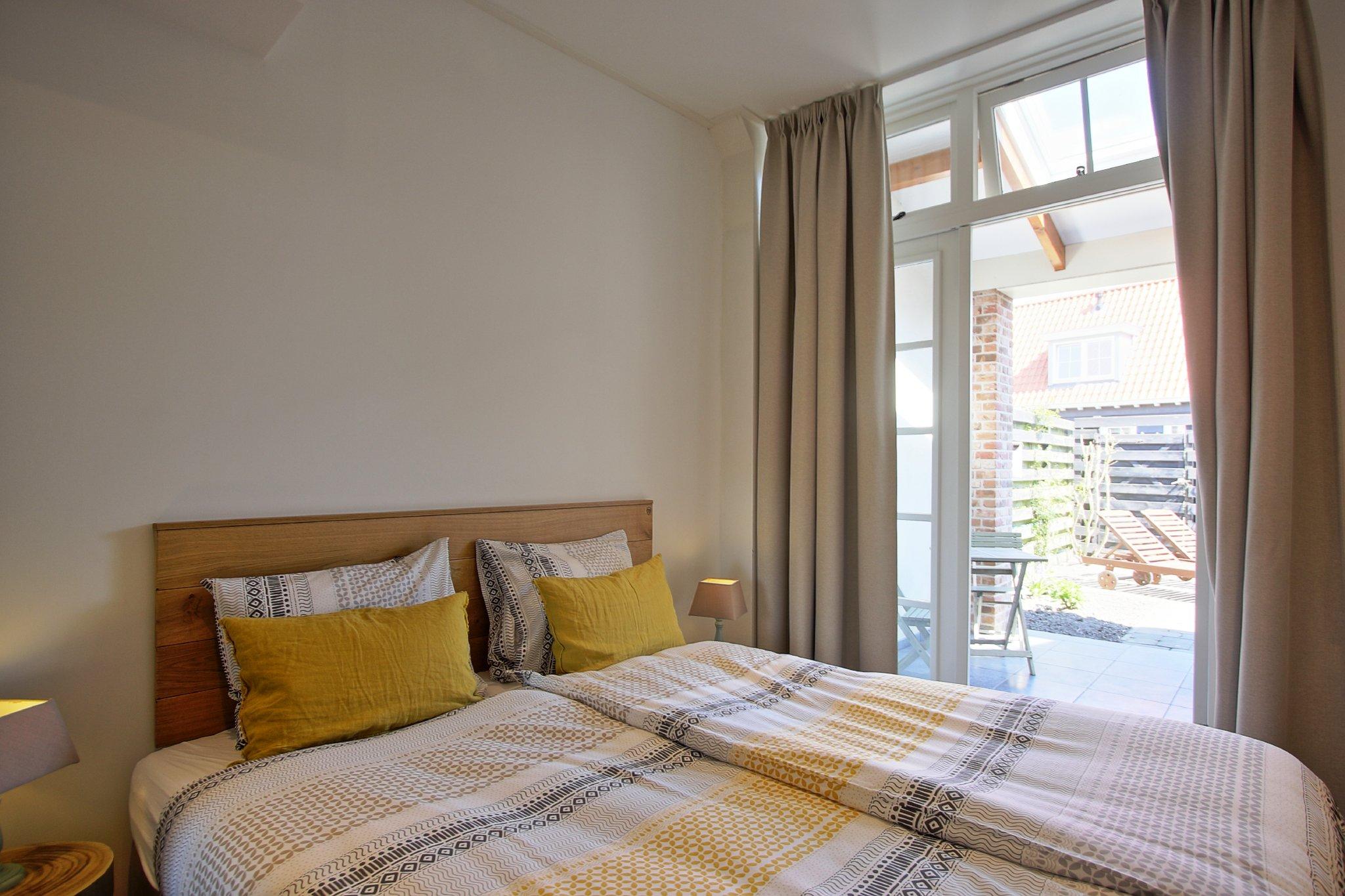 Schlafzimmer mit Flügeltüren zur Terrasse