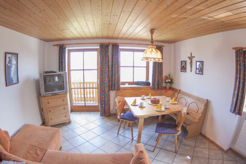 Wohnraum mit Eckbank und Zugang Balkon