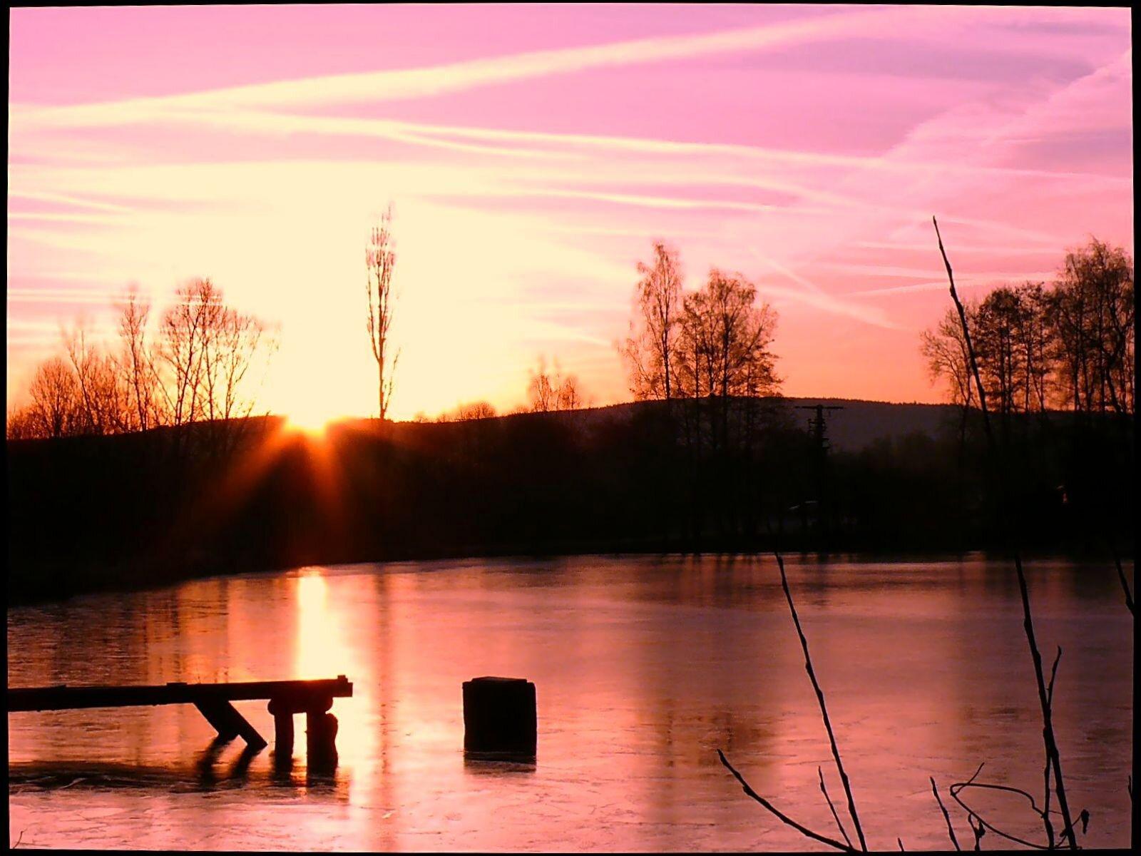 winterlicher Sonnenaufgang über dem See