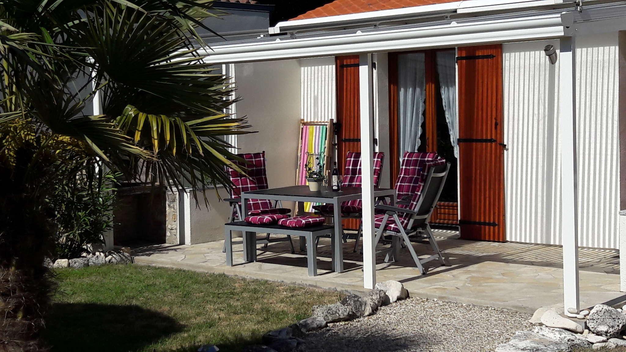 überdachte Terrasse und Grillkamin vorne