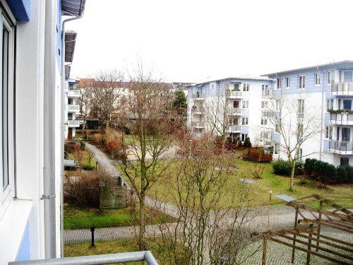 Blick vom Balkon in den grünen Innenhof