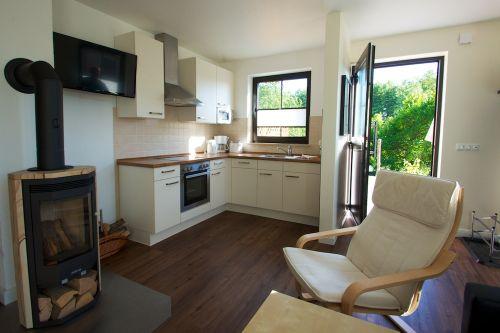 Das Wohnzimmer mit Küche und Kaminofen