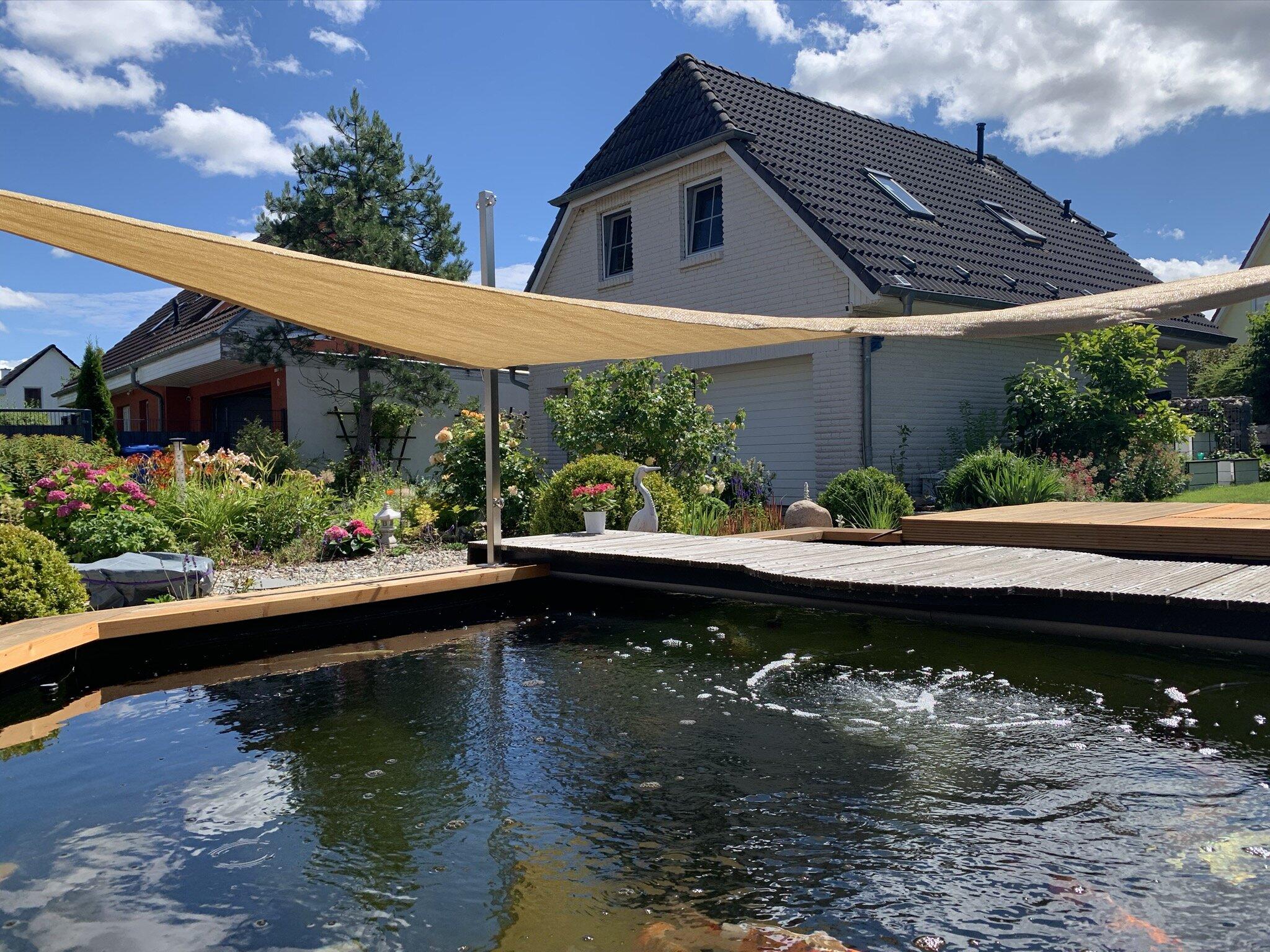 Blick auf den Gartenteich und Gästehaus
