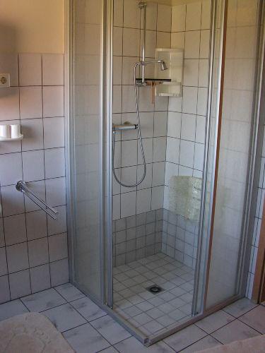 Bad mit ebenerdiger Dusche und Sitz