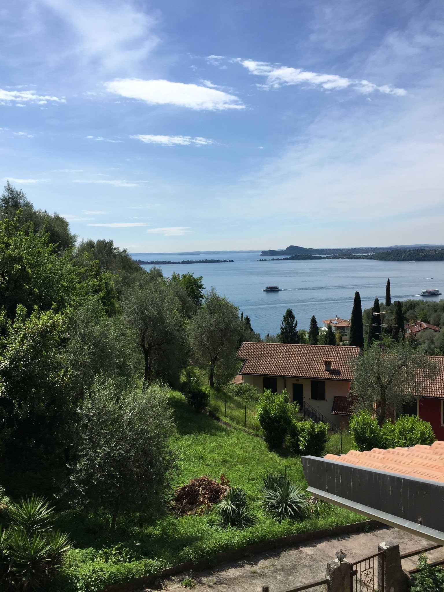 Blick von Wohnzimmer und Terrasse auf den Gardasee