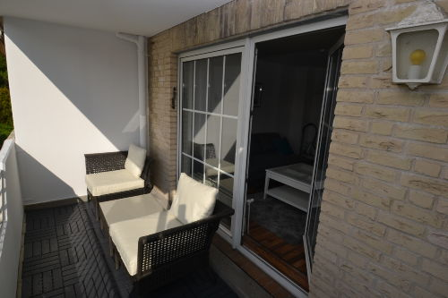 Sonniger Balkon mit Loungemöbeln