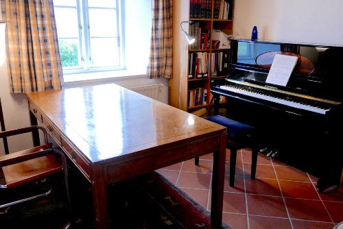 Arbeitszimmer mit Klavier und Sofa
