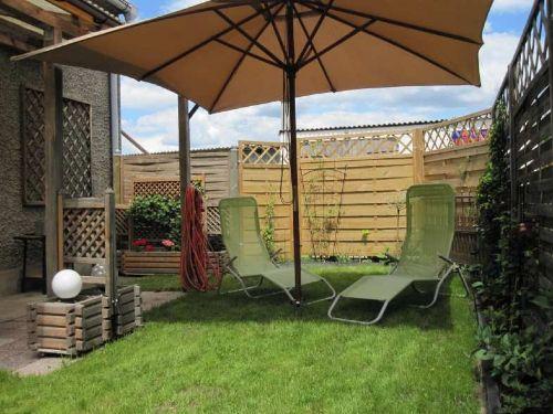 Garten mit Sonnenschirm und Liegestühlen