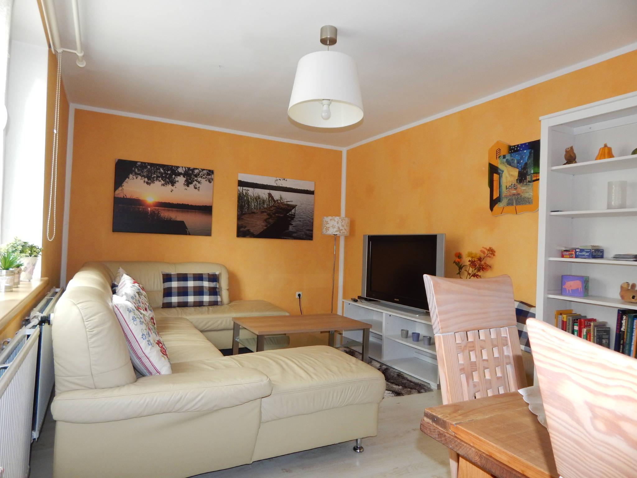 Wohnzimmer mit TV, Couch und Essplatz