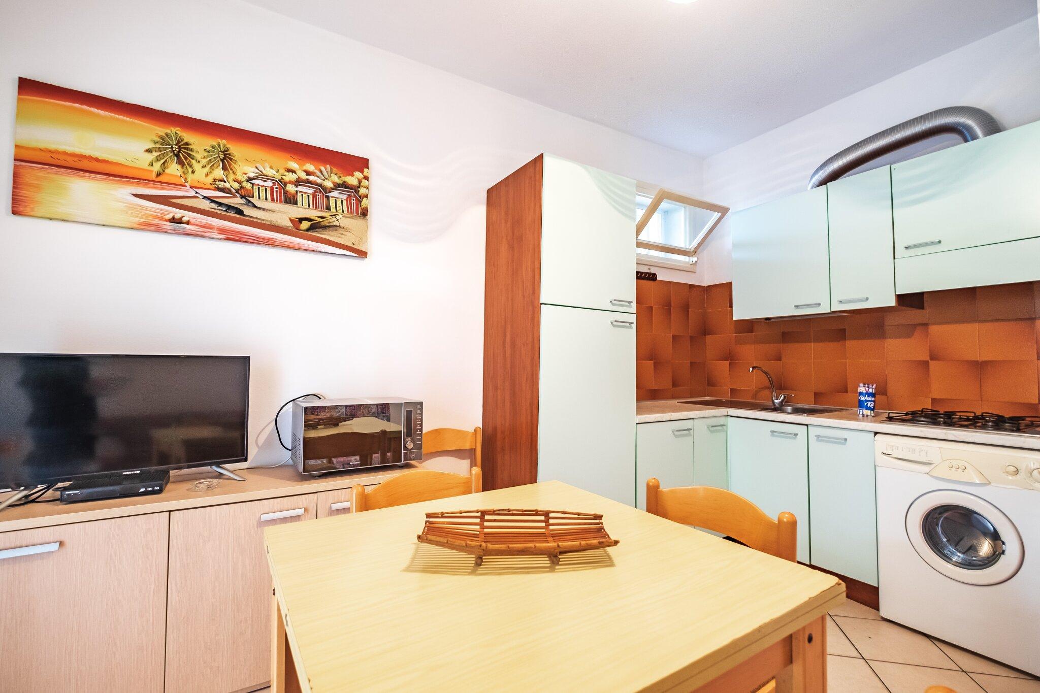 Wohnzimmer mit Schlafcouch und Küche