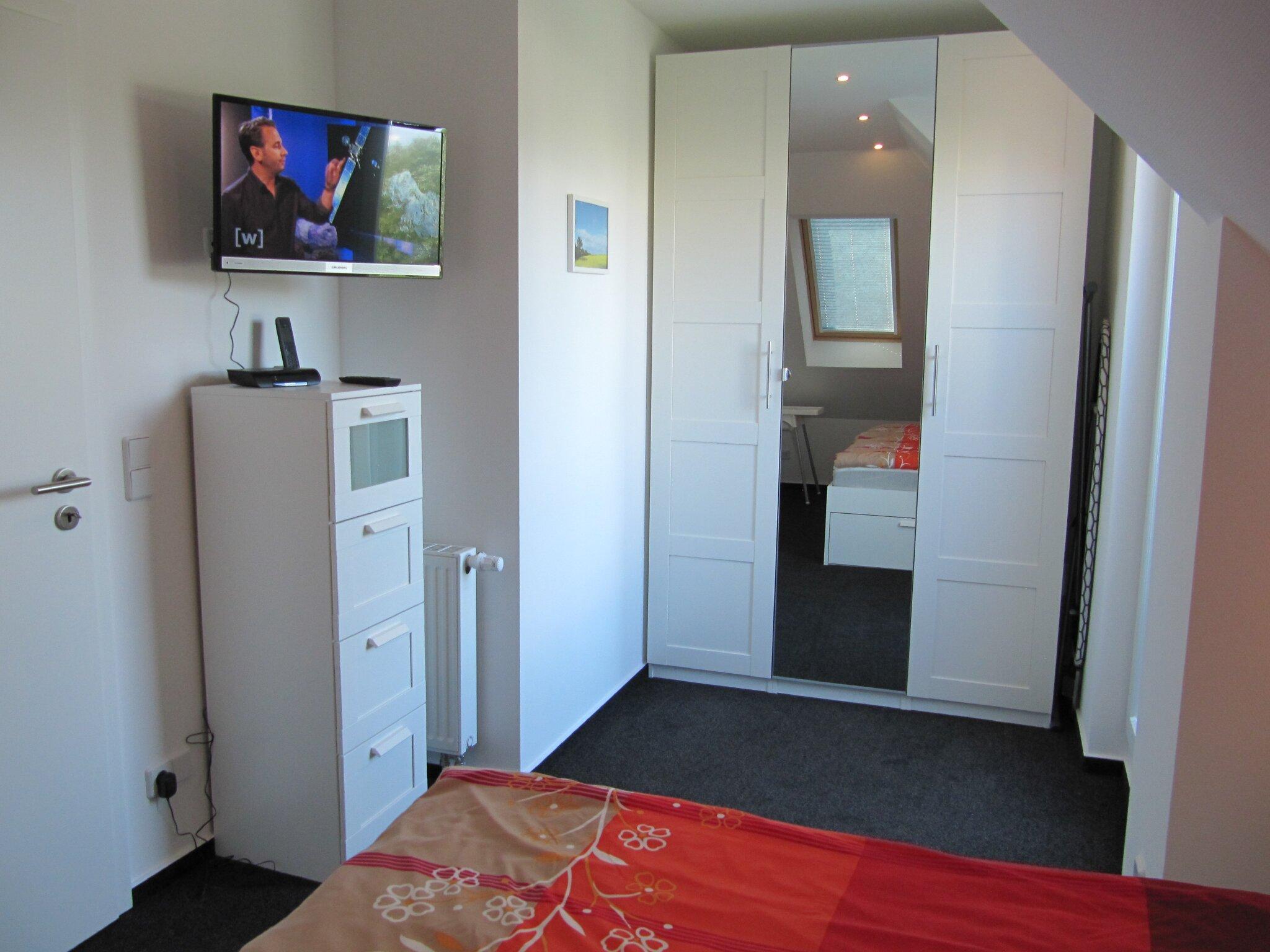 Schlafzimmer mit TV, Schrank u. Kommode