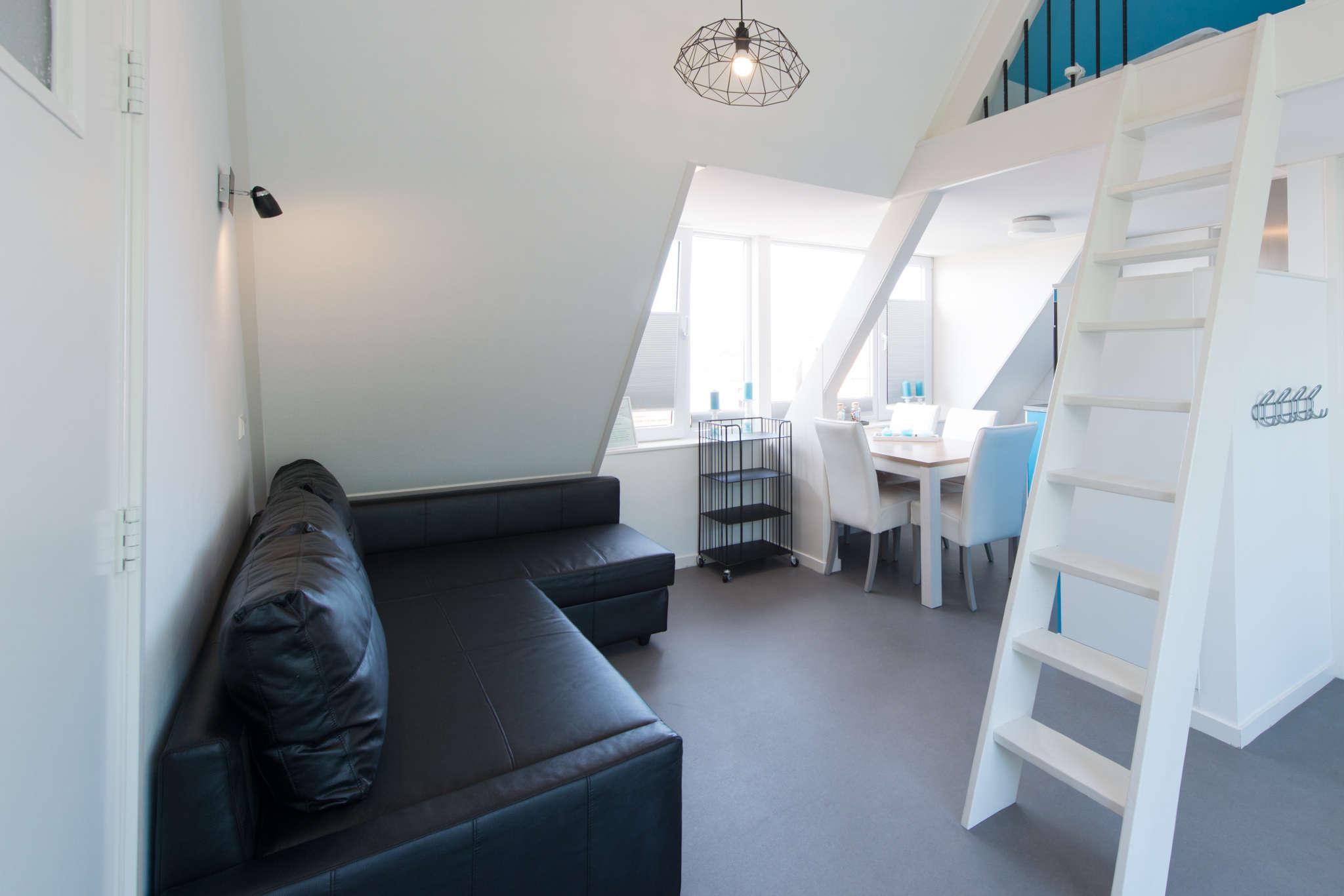 Wohnzimmer mit leiter zu Dachgeschoss
