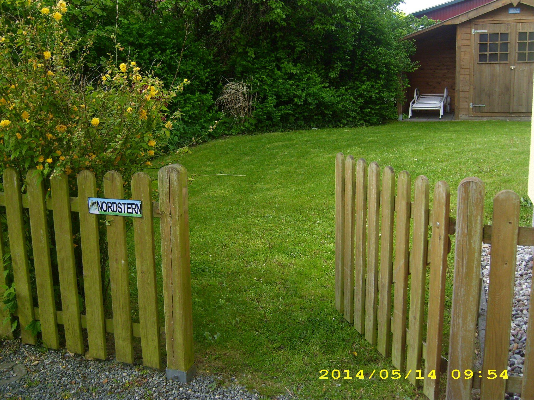 Gartenansicht mit Parkplkatz am Haus