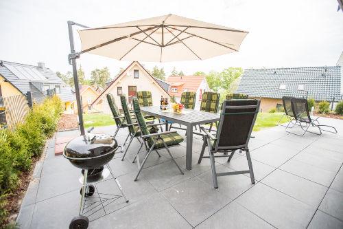 Moblierte Terrasse mit Liegen und Grill