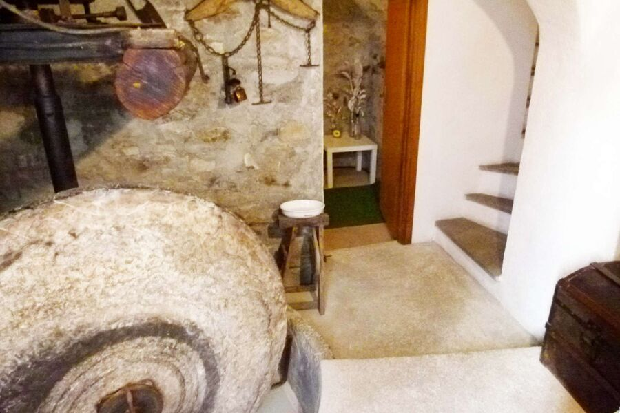 Eingang mit antiker Olivenpresse.