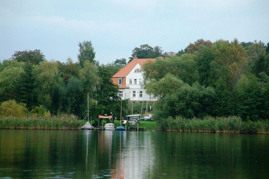 Blick über den See auf den Gutshof