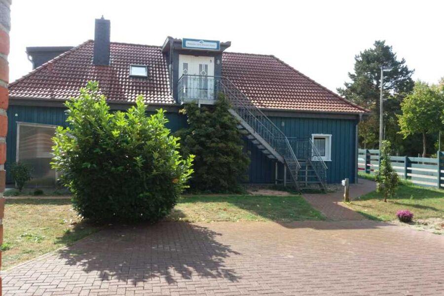 Innenhof mit Garten.Davor ein Parkplatz. Eine Trep