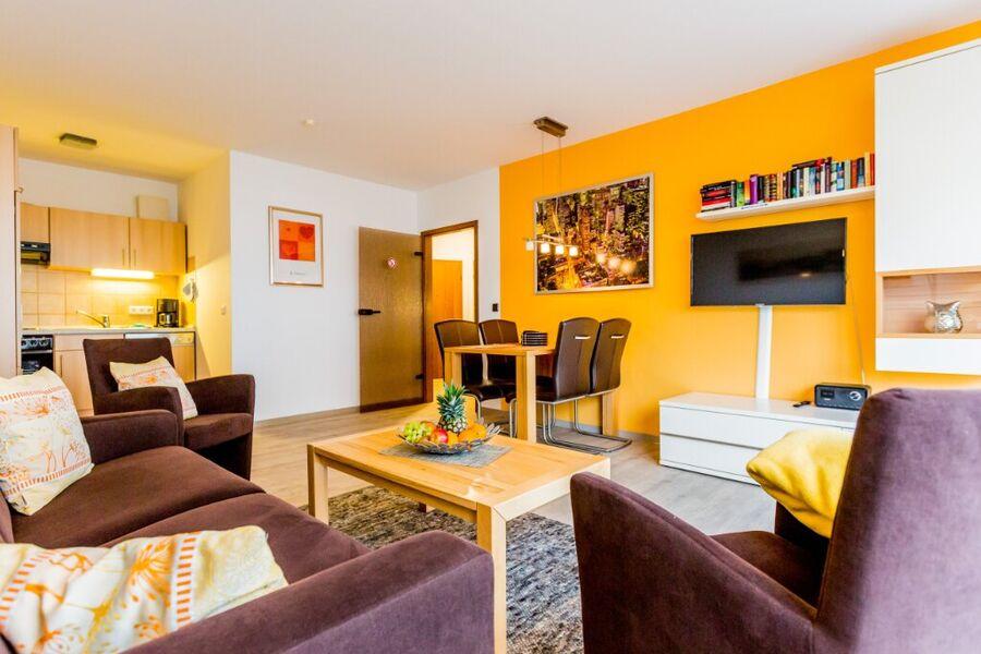 Wohnzimmer mit Sitzecke und Einbauküche