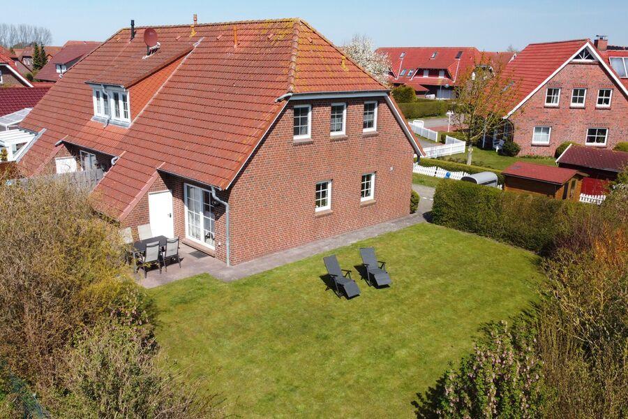 Sicht auf  Haus, Terrasse und Garten.