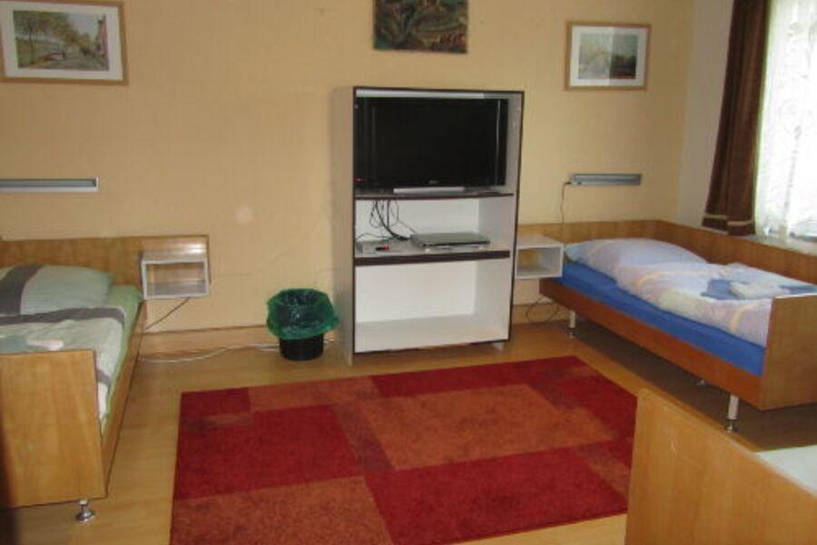 Schlafzimmer 1 mit 3 Einzelbetten und TV