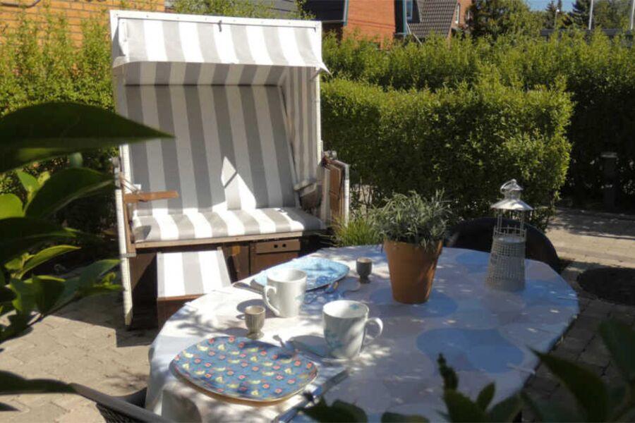 Terrasse mit Strandkorb, grossem Tisch und 2 Stühl