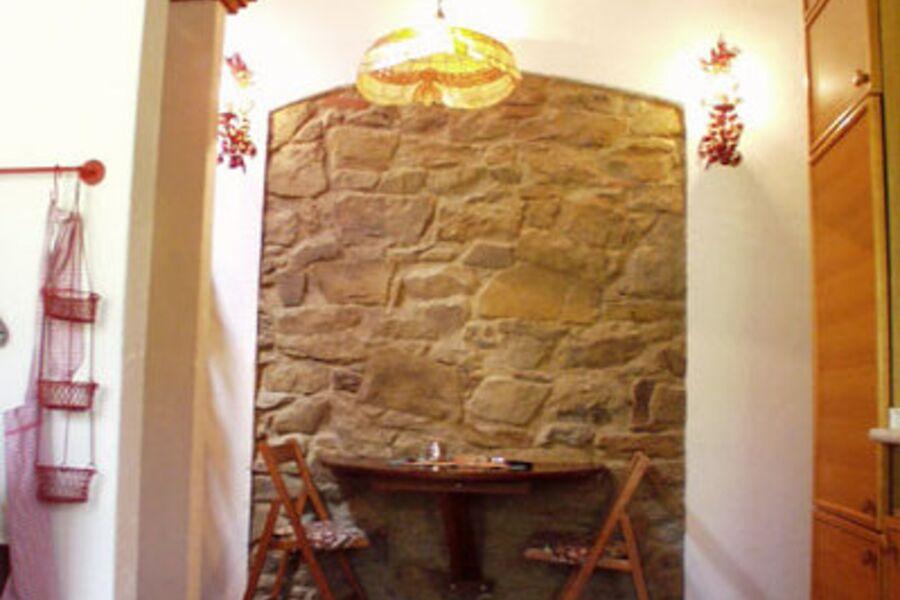 Der Esstisch vor einer alten Steinwand