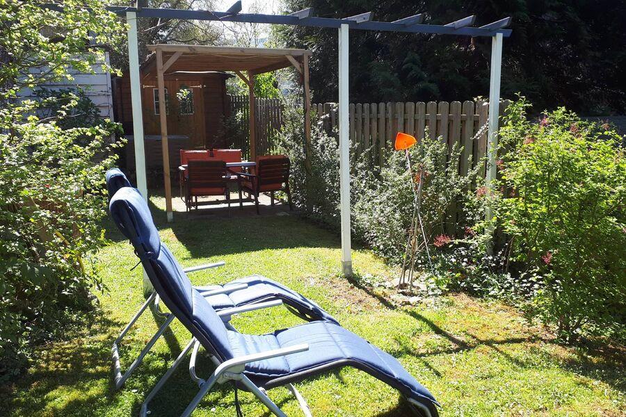 Pavillon und Sonnenliegen im Garten