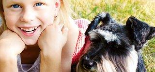 Mädchen mit Hund im Gras