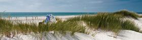 Strandkorb in den Dünen - Im Hintergrund das Meer
